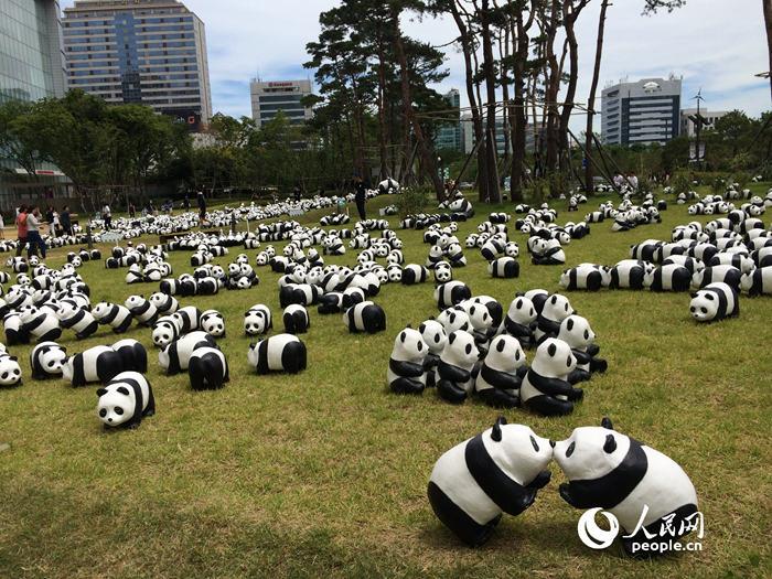 人民网首尔7月17日电(王昱祺 李美林)7月3日至30日,1600熊猫+主题展览在乐天世界大厦草坪花园和石村湖水公园举行。憨态可掬的熊猫玩偶吸引了大量民众前来观赏。   走进位于乐天世界大厦地下一层的AVENUEL广场,便会看到极具韩国特色的十七只熊猫玩偶,其中有顶着簸箕的、敲着长鼓的,还有穿着跆拳道服的。除了这些以韩国传统文化为主题创作的特别版熊猫玩偶外,在乐天世界大厦外的草坪花园上也可一睹熊猫玩偶的风采。在石村湖水公园里还摆放着享受日光浴的熊猫玩偶、正在野餐的熊猫玩偶、正在野营的熊猫玩偶、表