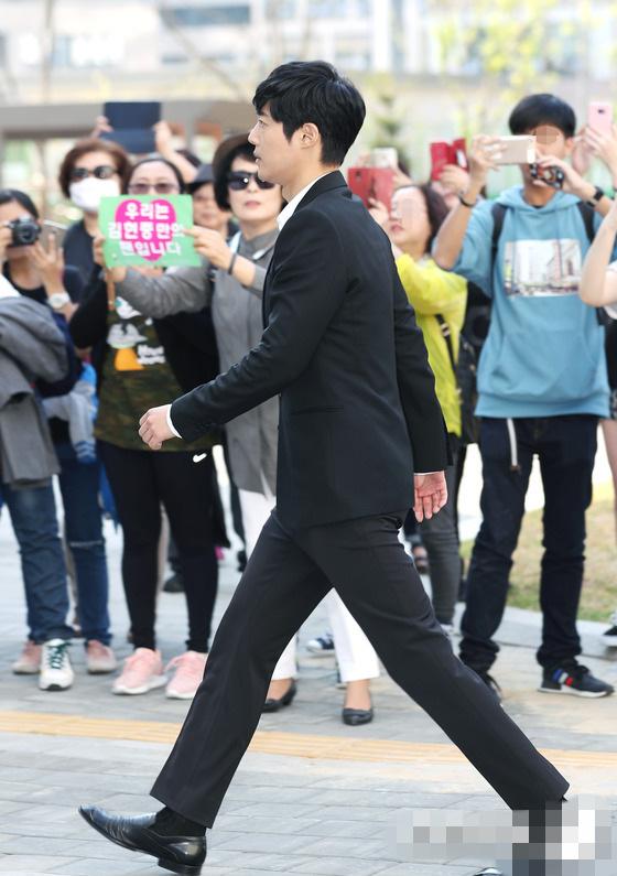 天,金贤重身穿黑色西装现身,表情严肃,支持他的粉丝手举应援条图片