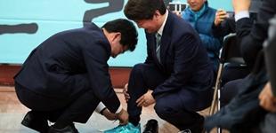 安哲秀竞选首尔市长 前对手为其系鞋带应援