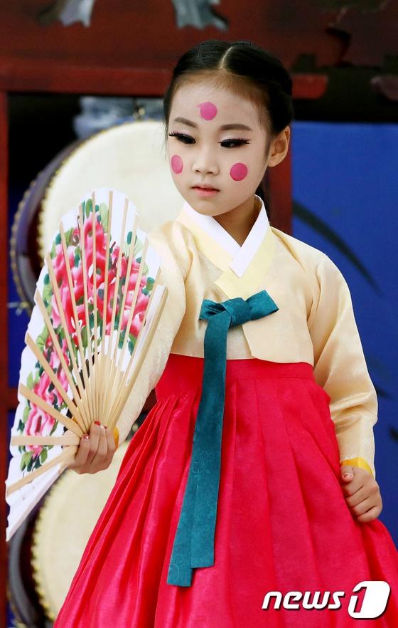人民網訊 據韓媒NEWS1報道,當地時間29日上午,安東國際假面舞節在慶尚北道安東假面公園連續舉辦的第二天,來自某藝術團的孩子們在舞台上進行傳統歌舞表演。她們身穿五顏六色的傳統韓服,特色妝容裝點著節日喜慶。(圖片來源:韓媒NEWS1)   文體相關新聞延伸閱讀