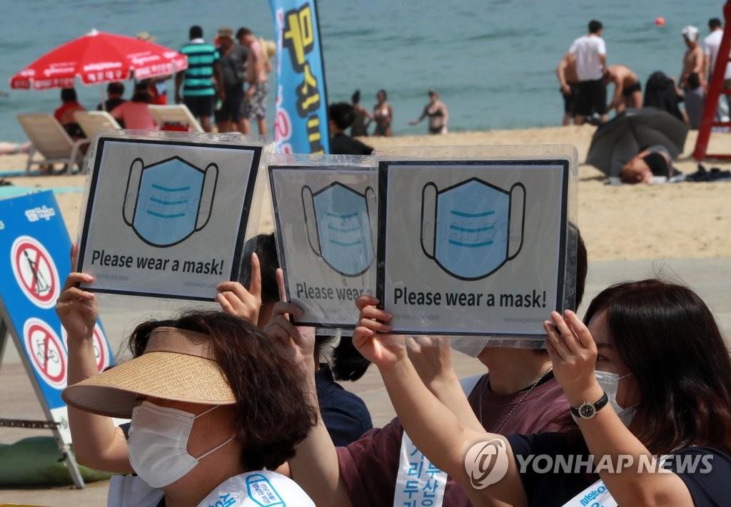 7月5日,在釜山市海云台海水浴场,市民呼吁访客佩戴口罩。图源:韩联社